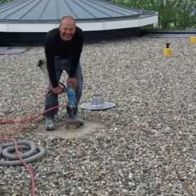 Marc boort een gat op het dak in Tuitjenhorn