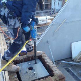 Maarten boort 4 gaten 1.5m diep op een schoorsteen